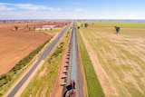 A drone image of a railway line under construction, with paddocks either side.