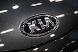 The KIA logo is seen up close on a charcoal grey car.