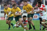 An Australian rugby union international puffs his cheeks out as he tries to break a tackle in a match against Japan.