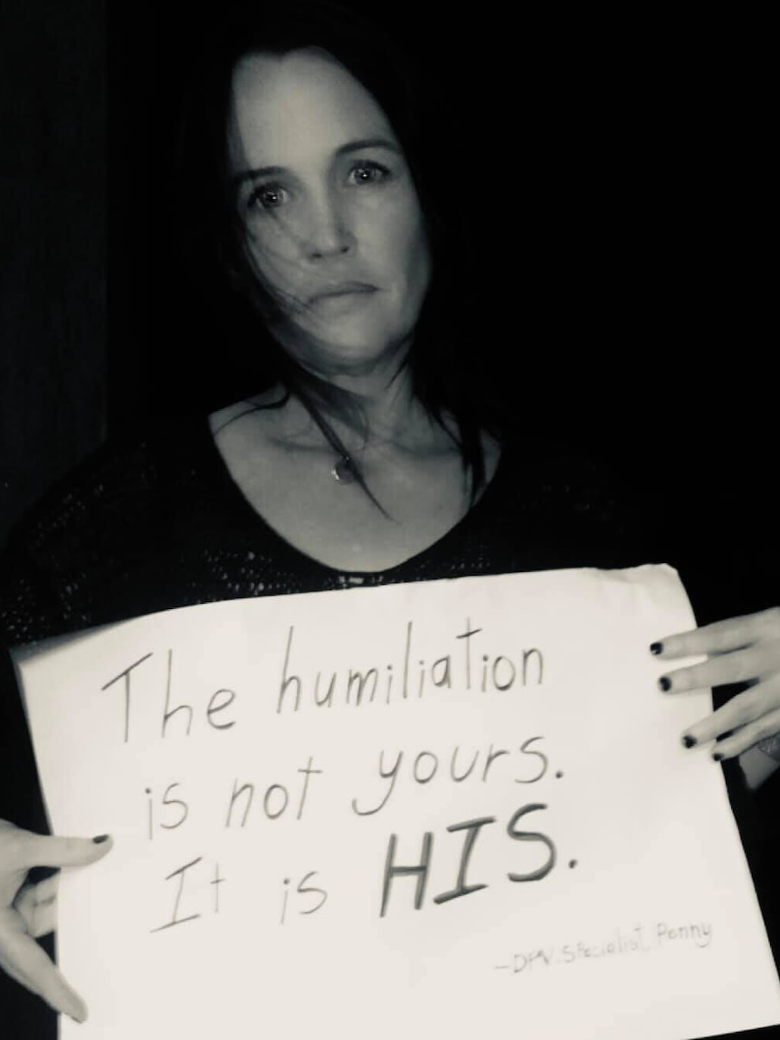 """a black and white photo of a woman holding a placard saying """"the humiliation is not yours, it is his"""""""