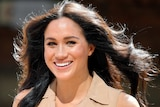 A close up photo of Meghan Markle in bright light with her black hair blowing in the wind.