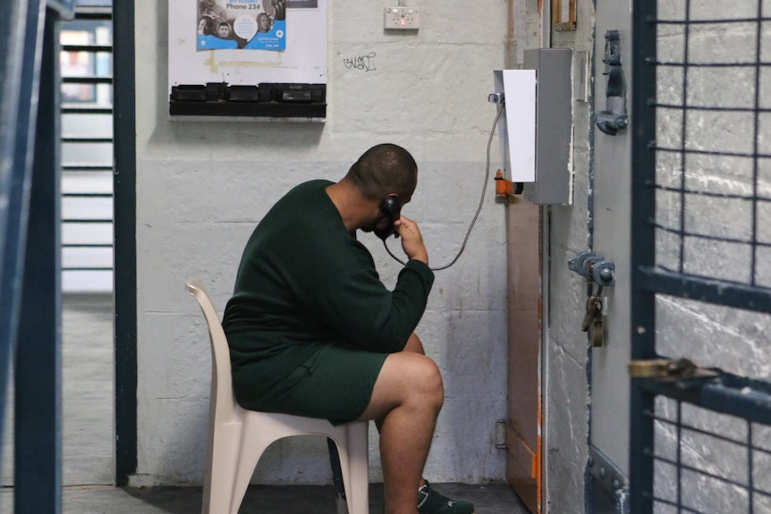 An inmate sits on a chair talking on a landline telephone.
