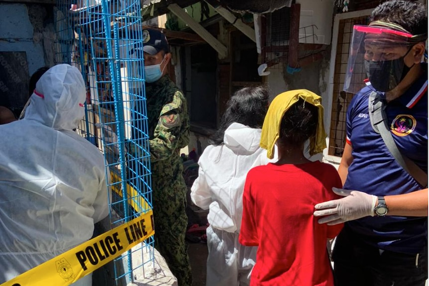 A man in PPE in a slum, with a young boy in front of him with his face covered by a towel
