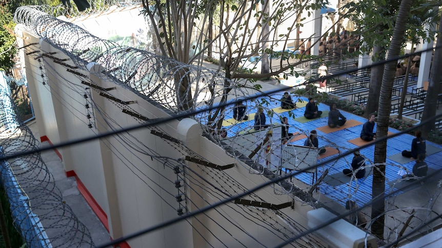 Thai women prisoners attend a yoga class behind high razor wire.