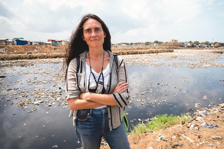 A woman stands in front of a polluted river.