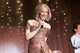 The actress in sequined floor-length gown and blonde bob, smiling and holding mic, on stage.