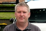 A man in a grey t-shirt stands outside with a white van behind him.