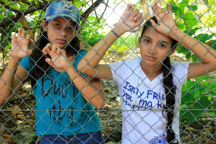 Two young refugee girls stand behind a barbed wire fence in nauru.