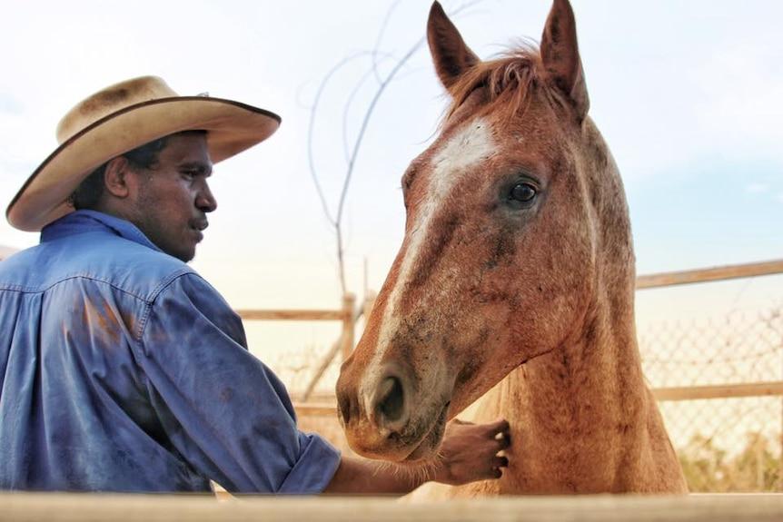 A man in a blue shirt and a bushman's hat with a horse.
