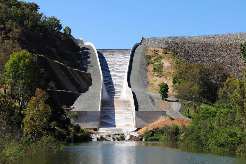 Water gushes from a dam into a river.