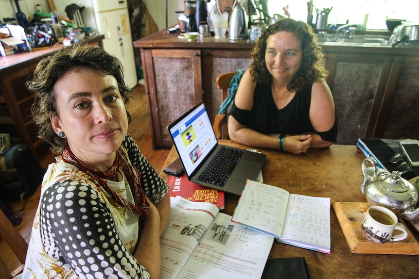 Two women sit with a laptop and exercise books during a Mandarin lesson