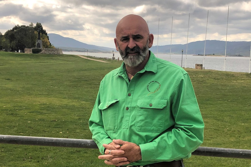 Olivier Kapetanakos stands at the edge of Lake Jindabyne wearing a green shirt and jeans. His hands are clasped.