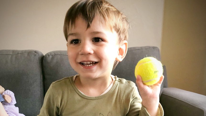A young boy holds a tennis ball in his left hand, in a story about left-handedness revealing family history.