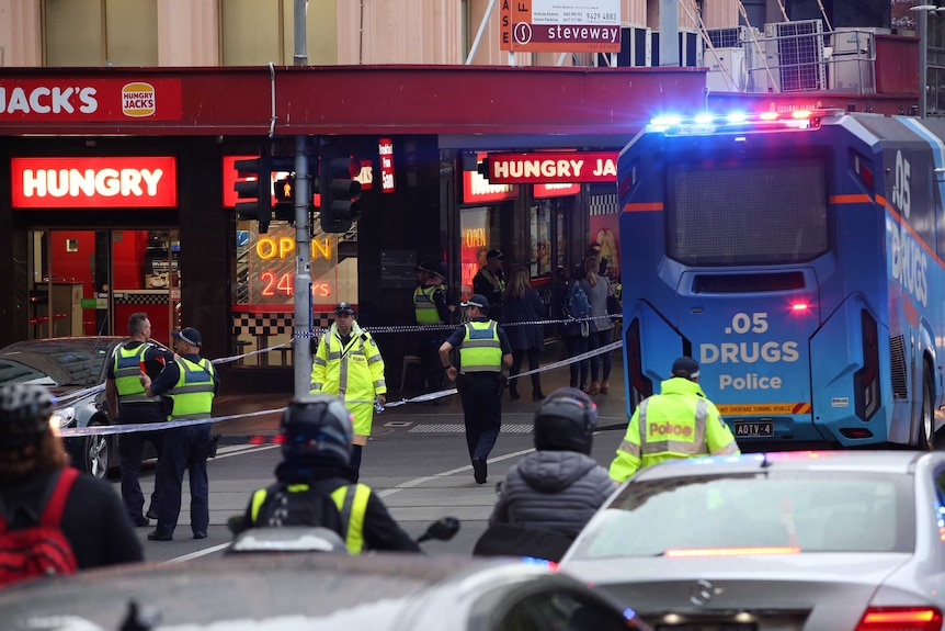 A drug testing bus and police tape is used to block Bourke Street.