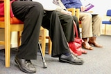 Photo of peoples legs and feet while they sit waiting in a waiting room