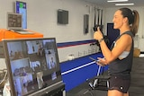 A woman hosts a gym working in front of a big Zoom video conference monitor.