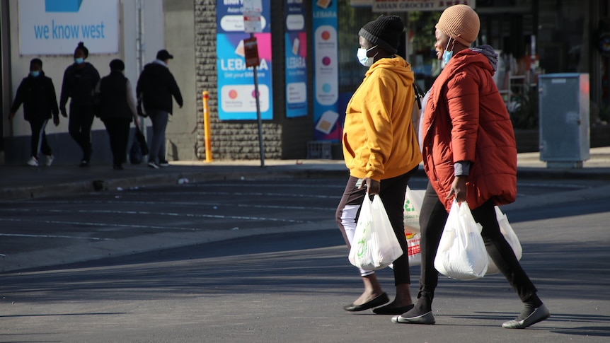 Two women holding shopping bags and wearing colourful puffer jackets and face masks walk across a road.