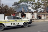 A police four-wheel drive ute outside a burnt-out petrol station