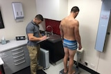 Athlete is weighed on digital scales by doctor as part of water loading research