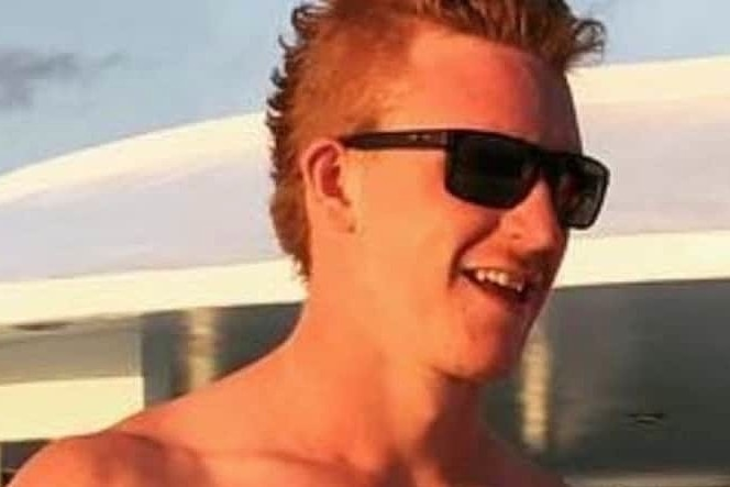 A young shirtless man wearing sunglasses.