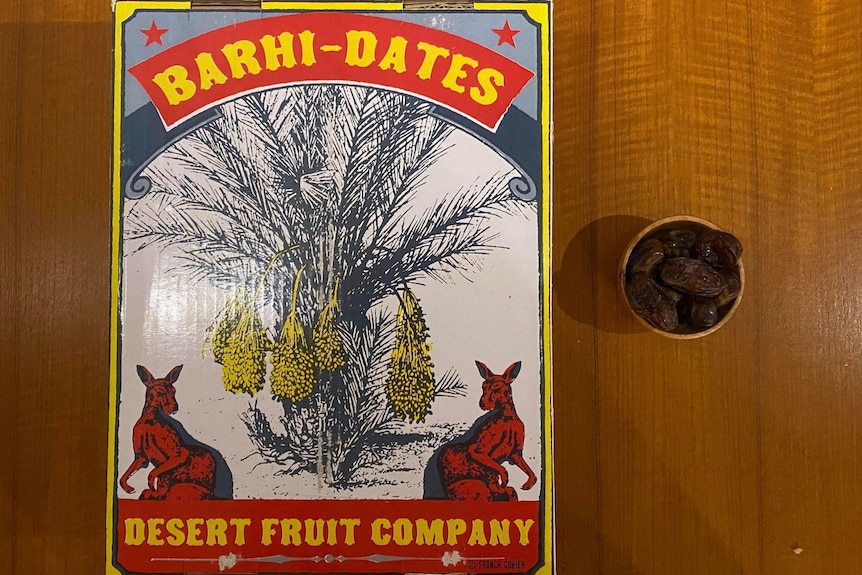 """A cardboard carton of dates with """"Barhi-Dates"""" and company name on top, with a small bowl of dates beside the box"""