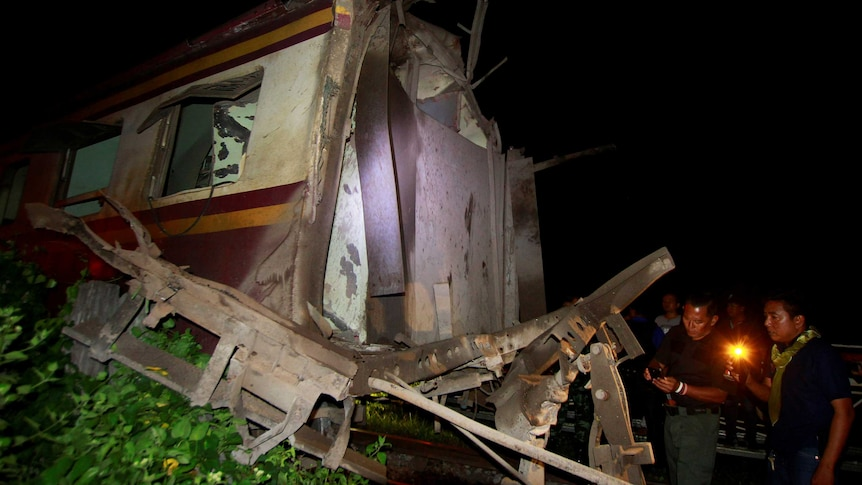 Military personnel inspect a derailed train carriage which was the site of a bomb blast in Pattani, Thailand.
