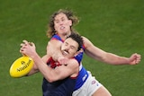 Two AFL players have a physical clash over a yellow ball on a green oval.