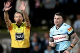 Josh Dugan runs next to referee Ben Cummins, who is holding both hands up above his head with his fingers outstretched