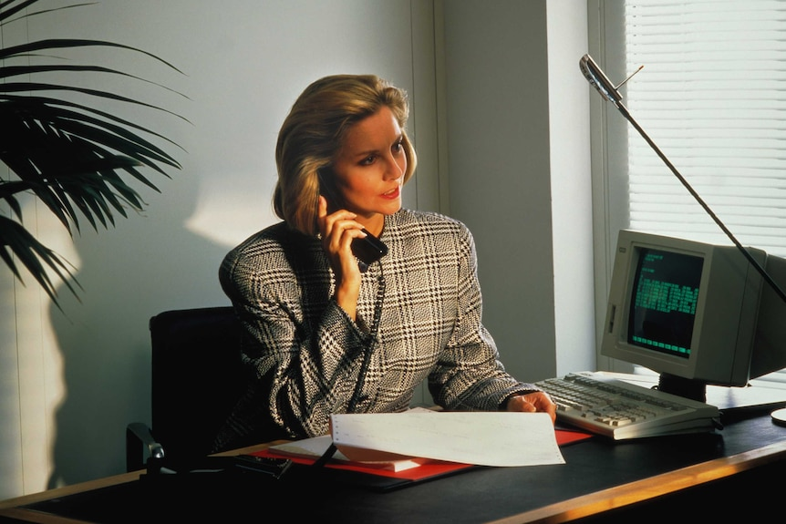 A woman in 1980s business attire sits at a desk with a telephone receiver to her ear.