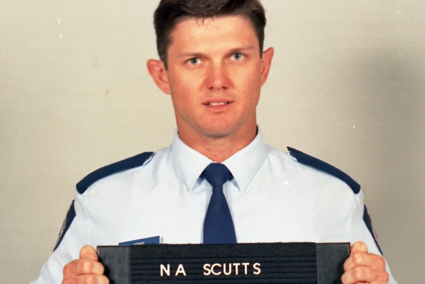 A fresh-faced police officer in blue shirt holds a black sign with his police number in white.