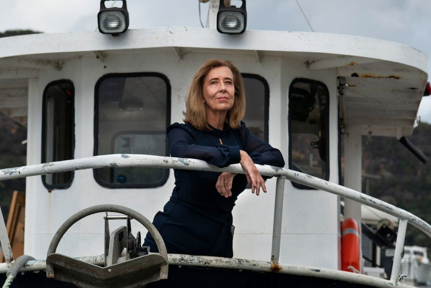 Kathyryn Heyman with shoulder length brown hair stands at end of a boat looking out over water.