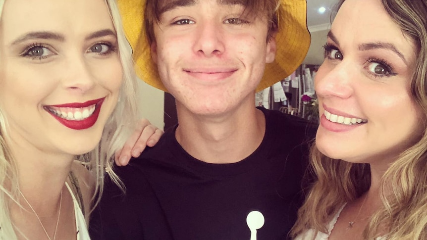 Young woman, teenage boy and adult woman side by side smiling