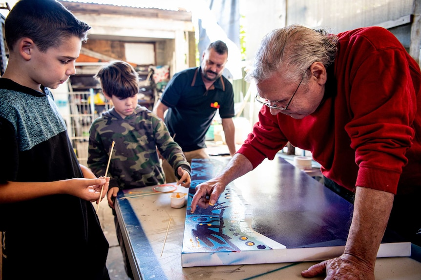 Danny leans over a painting on a table as his grandson watches on, with his son and other grandson in the background.