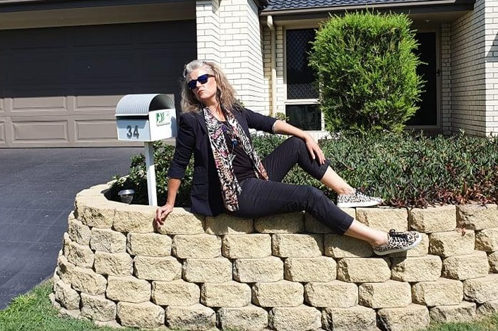 A woman sits on her garden and strikes a pose