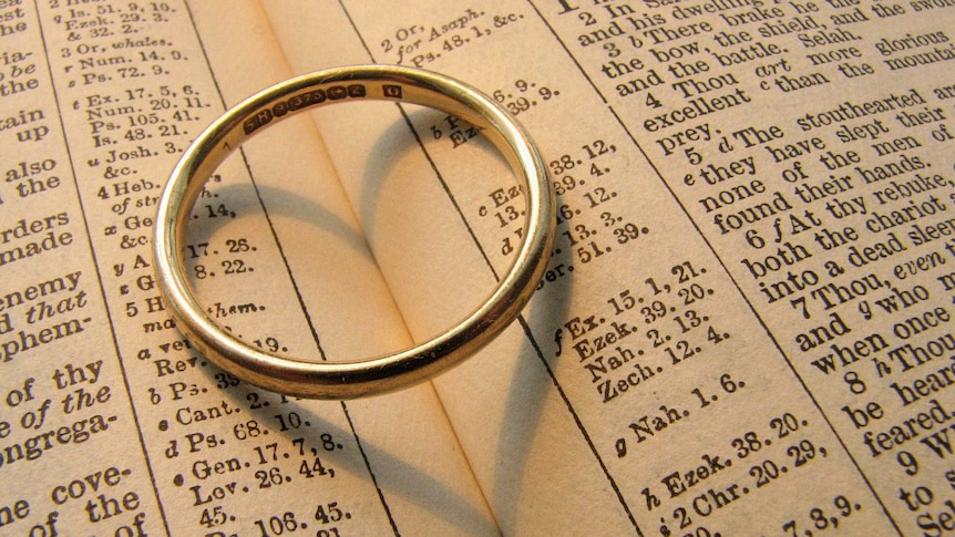 A wedding ring sits on a bible.