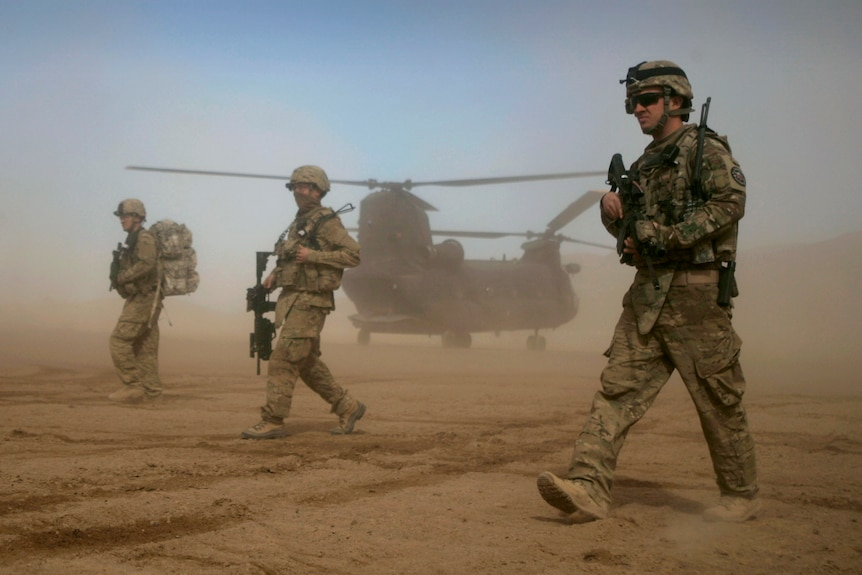 Three US soldiers in combat gear walking through a desert with a helicopter behind them
