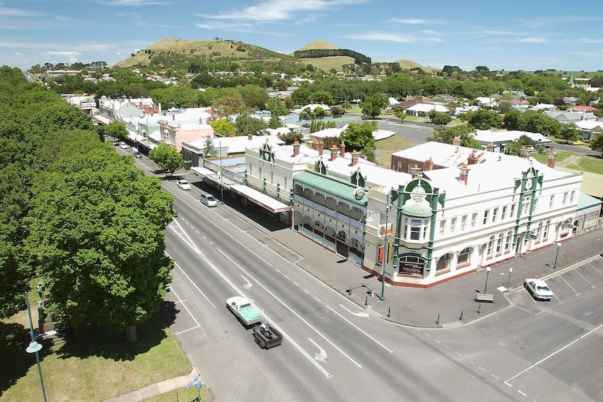 A view of a country town's buildings and trees from a high vantage point.