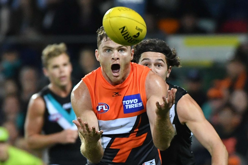Heath Shaw opens his mouth and eyes wide as he prepares to catch a yellow AFL ball in his outstretched arms.