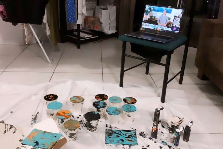 An arts and craft project arranged in front of a computer screen with a woman talking.