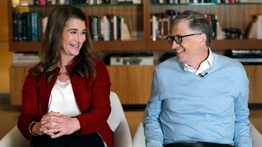 Melinda Gates smiles at Bill Gates, who is sitting next to her.