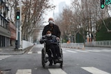 A man wearing a face mask pushes a woman on a wheelchair in Wuhan.