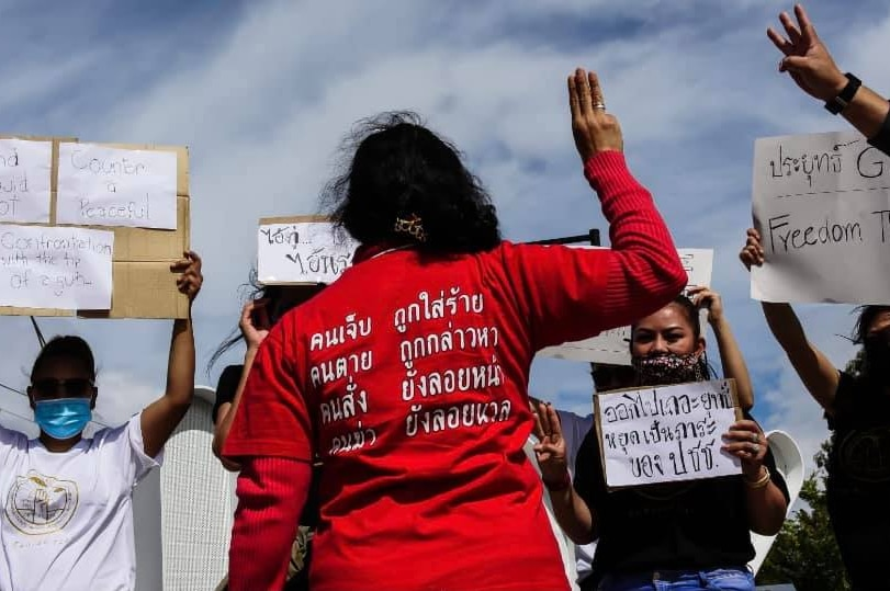 A woman holds up a three-finger salute and wears a red shirt with Thai script.