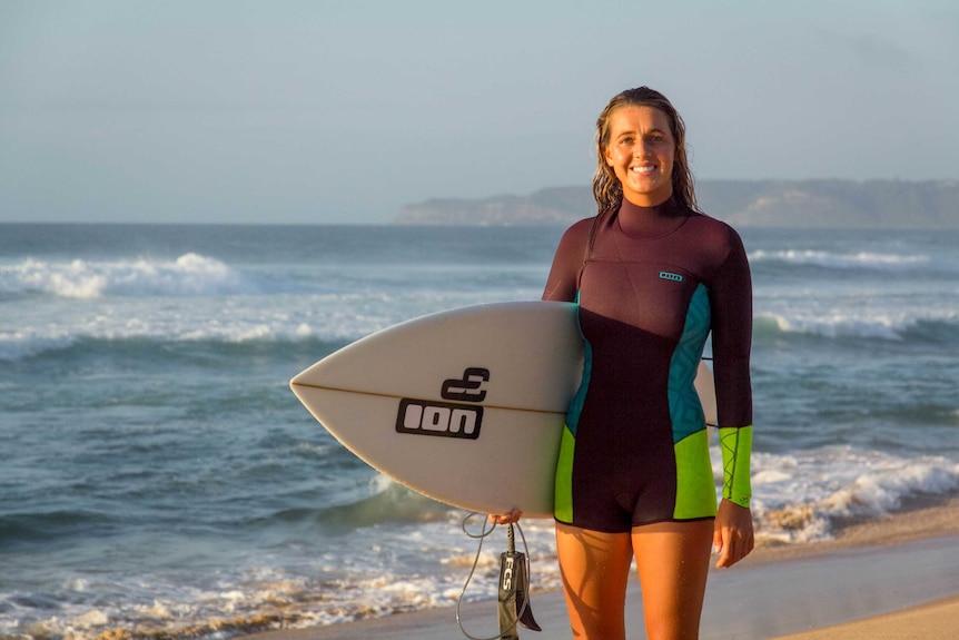 Philippa Anderson walks along Bar Beach with her surfboard.