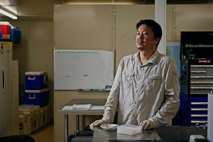 Dr Yusuke Fukuda stares across a research lab.