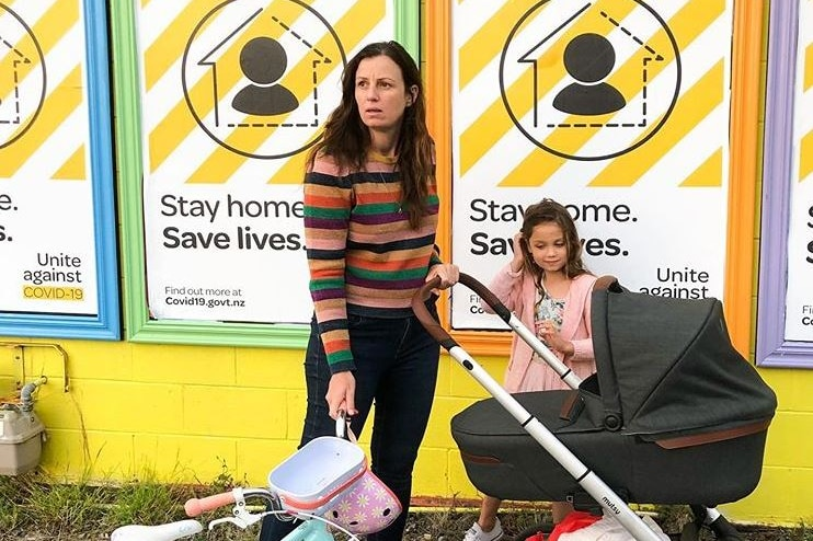 Anita Affleck pushes a pram and holds a child's bike in front of posters about coronavirus.