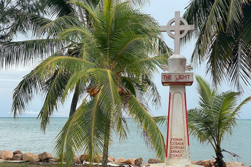 A monument on an island with the ocean and palm trees in the background.