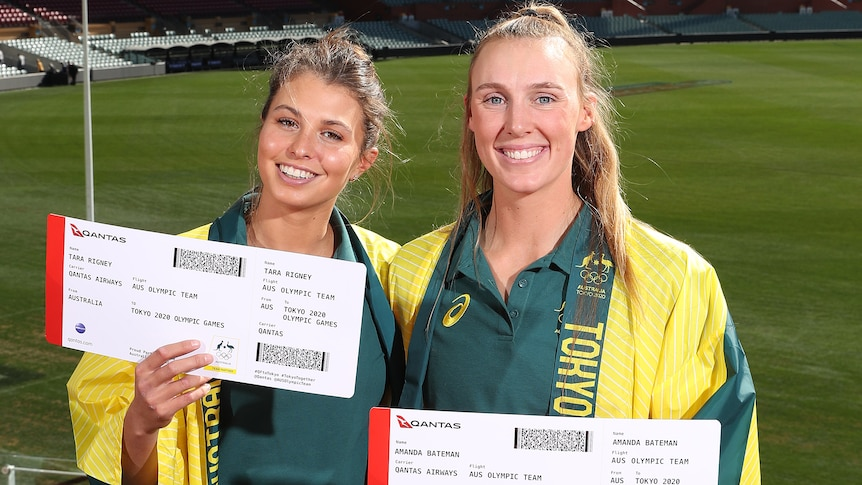 Two women holding large boarding boarding passes and wearing green and gold robes over green uniform shirts.