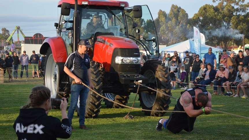 A man with big muscles has a chain around him and is pulling a bright red tractor.