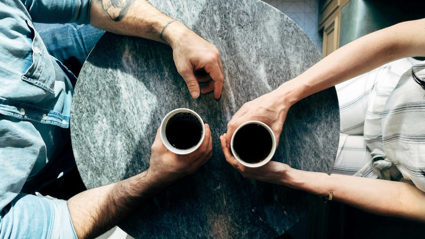 Aerial shot of couple at table holding a coffee each for a story about mental health struggles and relationships.