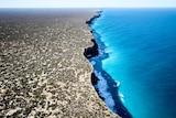 An aerial shot of cliffs next to the ocean.